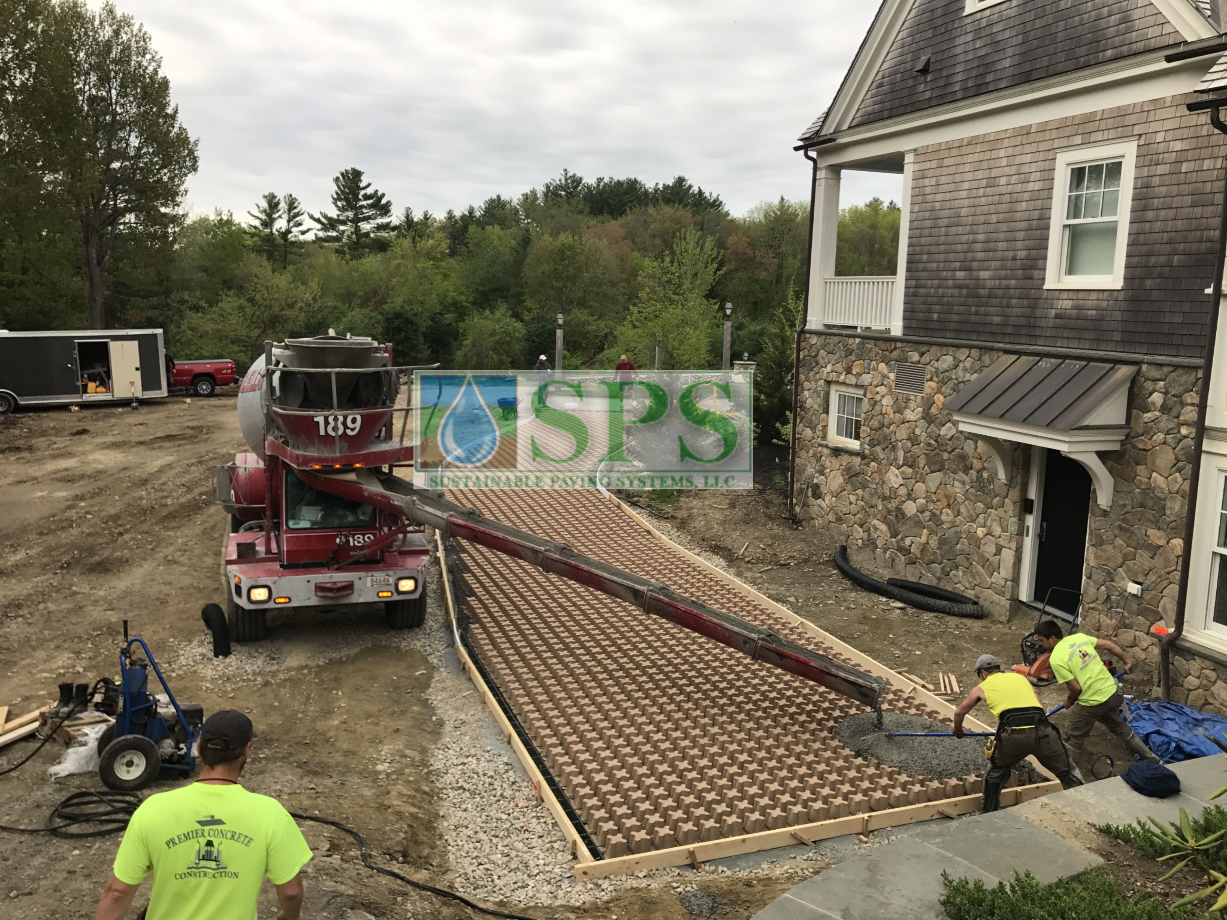 Concrete pour of Pervious Grasscrete Concrete onto the moulded pulp formers, being installed by Premier Concrete Construction at an Essex County estate in MA, with a view of the voids and the rebar reinforcement to provide strength for any heavy vehicles.