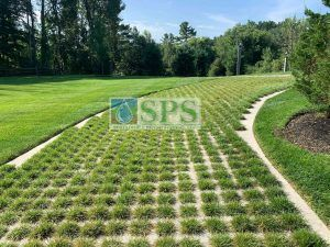 Long expansive view of finished installation of Partially Concealed Grasscrete on a drivewary for tradesmen and storm watermanagement in a Grand Estate in Essex Country MA.