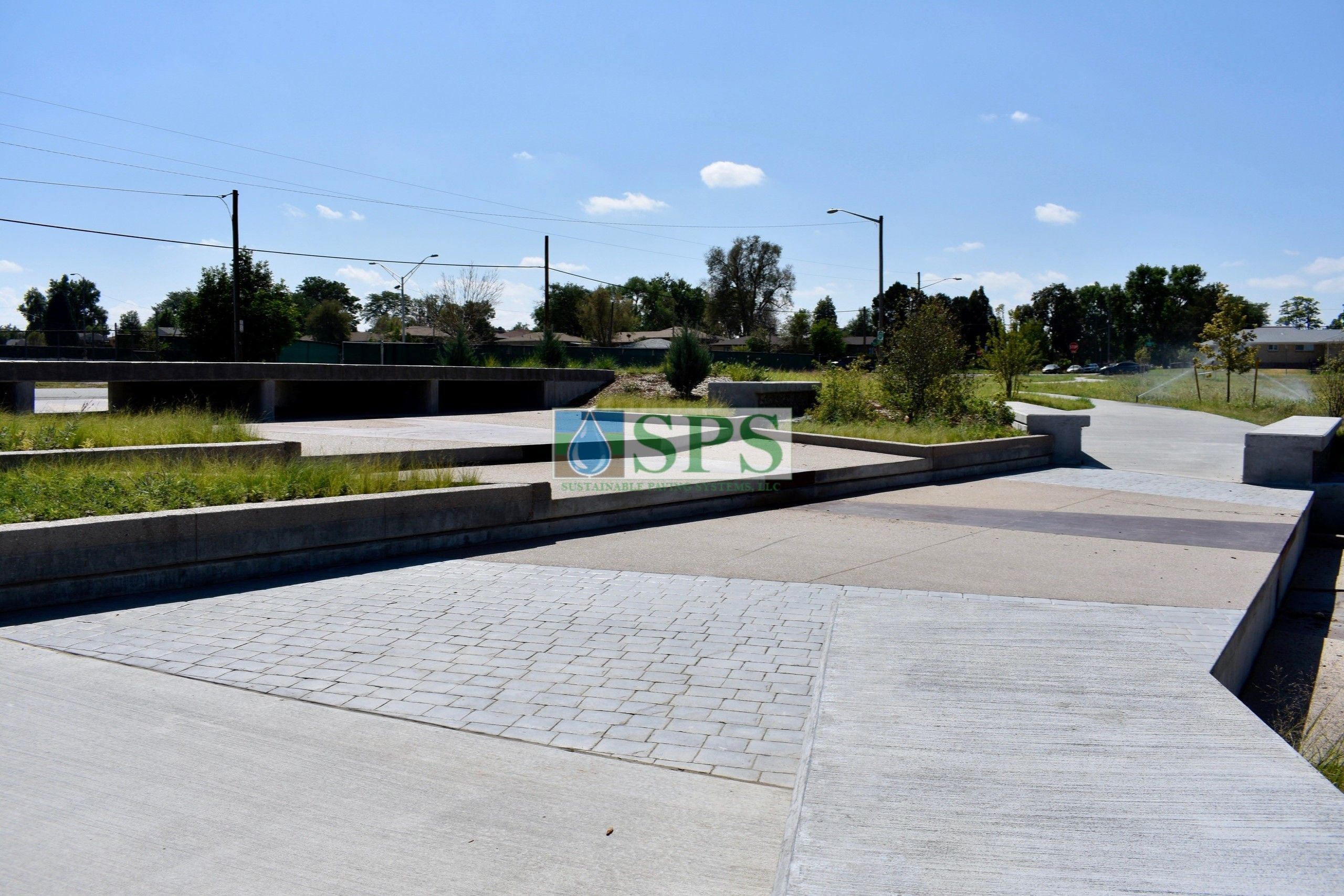 Gabion tiered drop structure detention pond located in Denver, CO that was planted with varying grasses for greenspace and stormwater management using Sustainable Paving Systems Partial Grasscrete System installation of a pervious monolithic cast-in-place concrete.