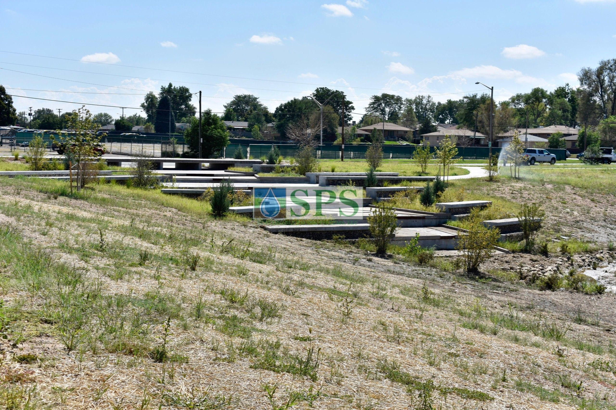 Long view of gabion tiered drop structure detention pond located in Denver, CO that was planted with varying grasses for greenspace and stormwater management using Sustainable Paving Systems Partial Grasscrete System installation of a pervious monolithic cast-in-place concrete.