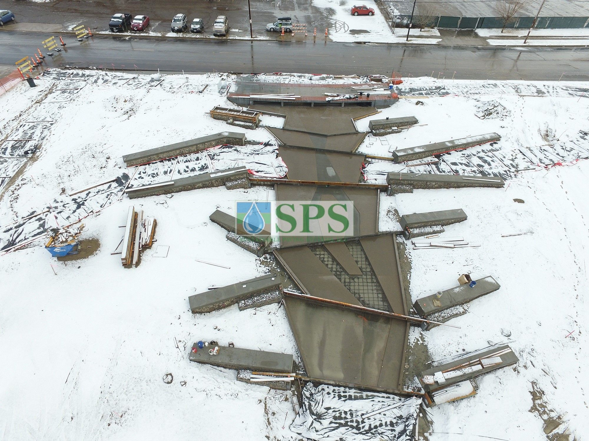 Overhead view of gabion tiered drop structure detention pond located in Denver, CO that was planted with varying grasses for greenspace and stormwater management using Sustainable Paving Systems Partial Grasscrete System installation of a pervious monolithic cast-in-place concrete.