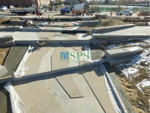Overhead view of Sustainable Paving Systems Partial Grasscrete System installation of a pervious monolithic cast-in-place concrete which is suitable for this gabion tiered drop structure detention pond located in Denver, CO that was planted with varying grasses for greenspace and stormwater management.