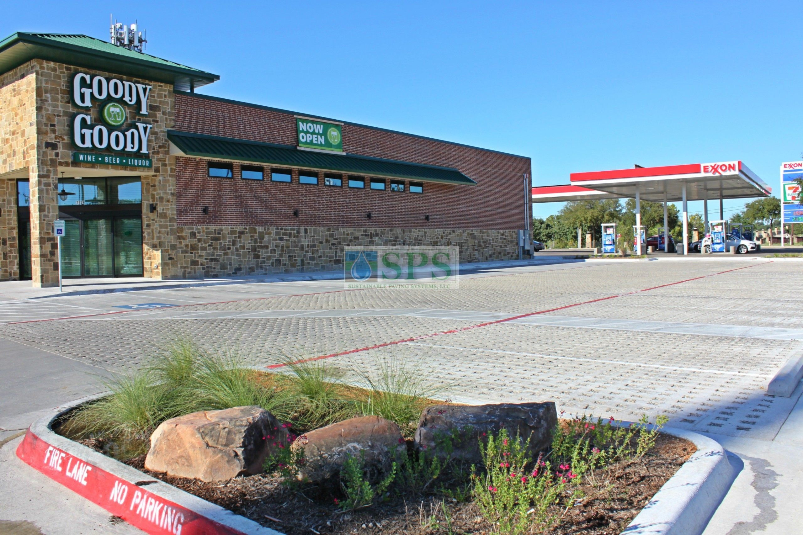 Wider view of the entrance and the parking lot of Goody Goody Liquor in Dallas, TX, featuring Grasscrete Stone Filled Systems installed by Texas Bomanite.